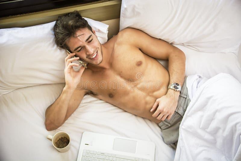 Shirtless muskul?s ung man i s?ng som talar p? mobiltelefonen royaltyfri fotografi
