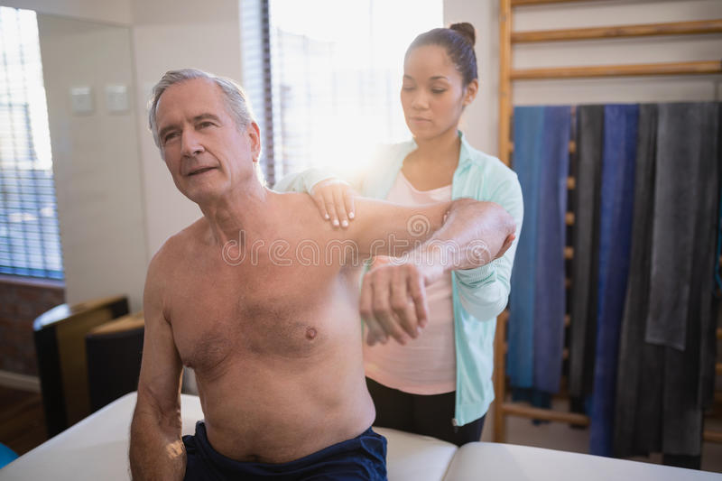 Shirtless senior male patient with arms raised receiving neck massage from female therapist. At hospital ward stock photos