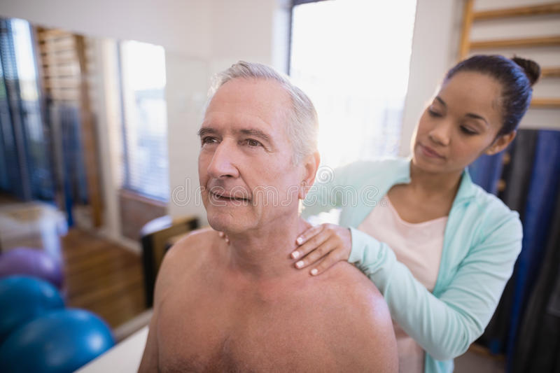 Shirtless senior male patient receiving neck massage from female therapist. At hospital ward royalty free stock photo