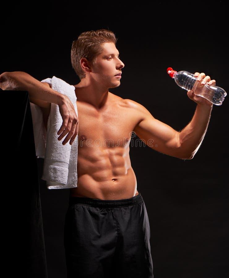 Shirtless sexigt ta för idrottsman vilar och dricksvatten efter genomkörare royaltyfria foton