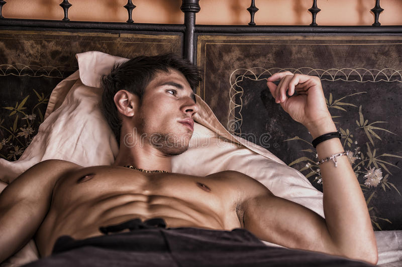 Shirtless male model lying alone on his bed stock photography