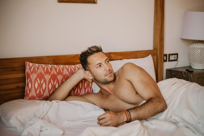 Shirtless male model lying alone on his bed in his bedroom, looking away with a seductive attitude.Carefree guy stock photo