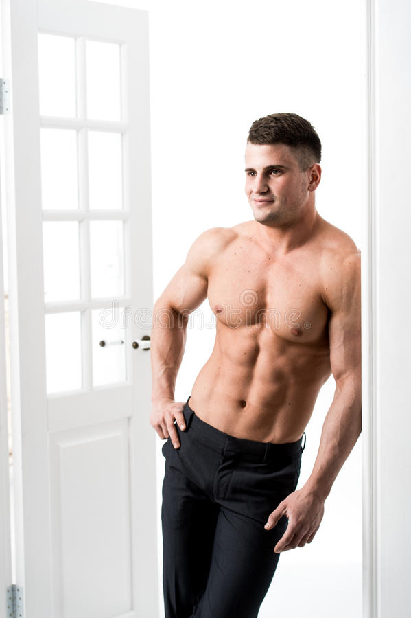 Shirtless male model standing in the doorway home interior, looking away with a seductive attitude. Athlete man standing in the doorway home interior royalty free stock image