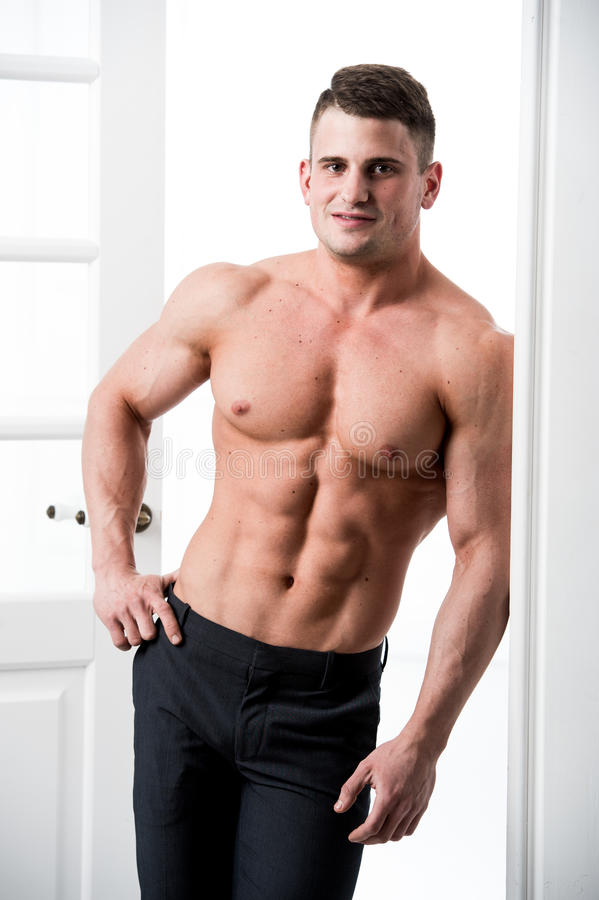Shirtless male model standing in the doorway home interior, looking to camera with a seductive attitude. Athlete man standing in the doorway home interior royalty free stock photos