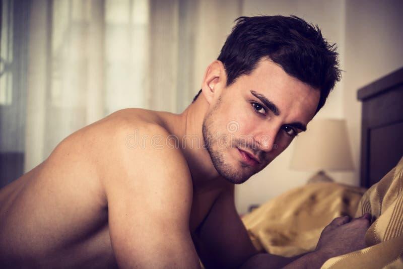 Shirtless sexy mannelijk model die alleen op zijn bed liggen royalty-vrije stock fotografie