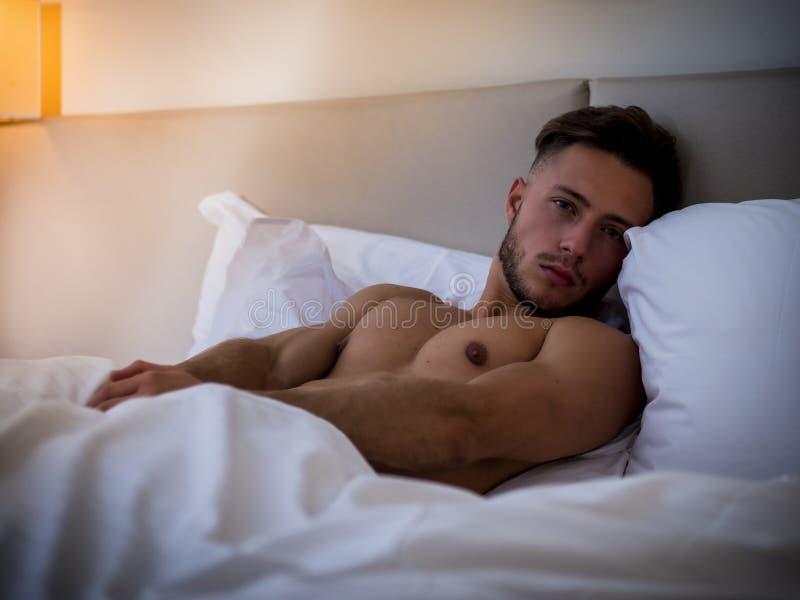 Shirtless sexy mannelijk model die alleen op zijn bed liggen stock foto