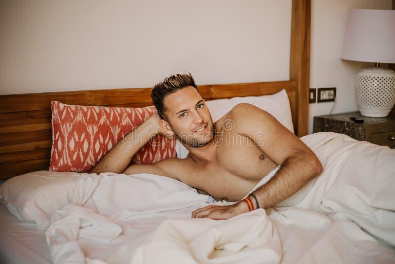 Shirtless sexy mannelijk model die alleen op zijn bed in zijn slaapkamer liggen, die de camera met een verleidelijke houding beki royalty-vrije stock afbeeldingen