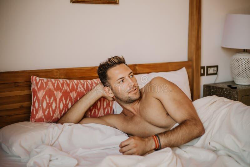 Shirtless sexy mannelijk model die alleen op zijn bed in zijn slaapkamer liggen, die weg met een verleidelijke houding kijken Onb stock foto