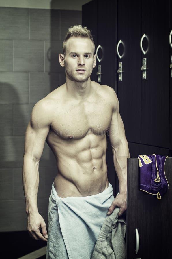 Shirtless spier jonge mannelijke atleet in gymnastiekkleedkamer stock afbeeldingen