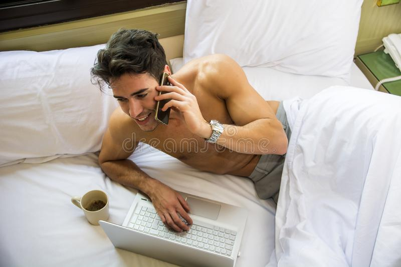 Shirtless spier jonge mens in bed die op celtelefoon spreken stock foto