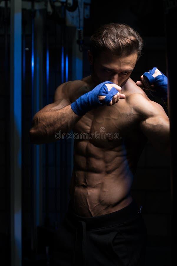 Shirtless spierbokser met ponsenzak in gymnastiek stock foto's