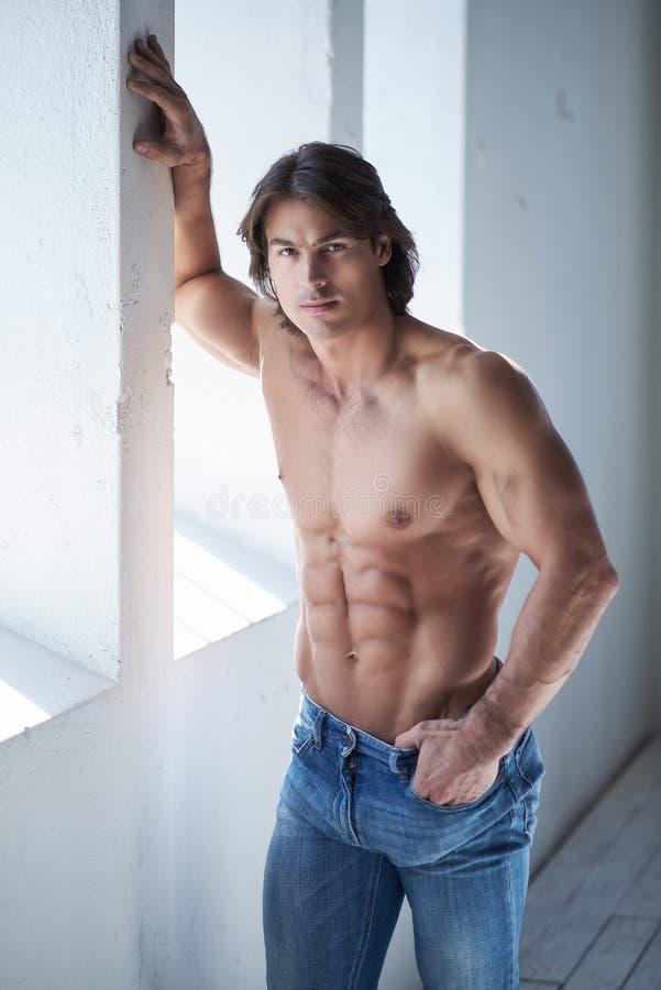 Shirtless stilig man med en perfekt benägenhet för muskulös kropp på en vägg i en studio som ser en kamera fotografering för bildbyråer