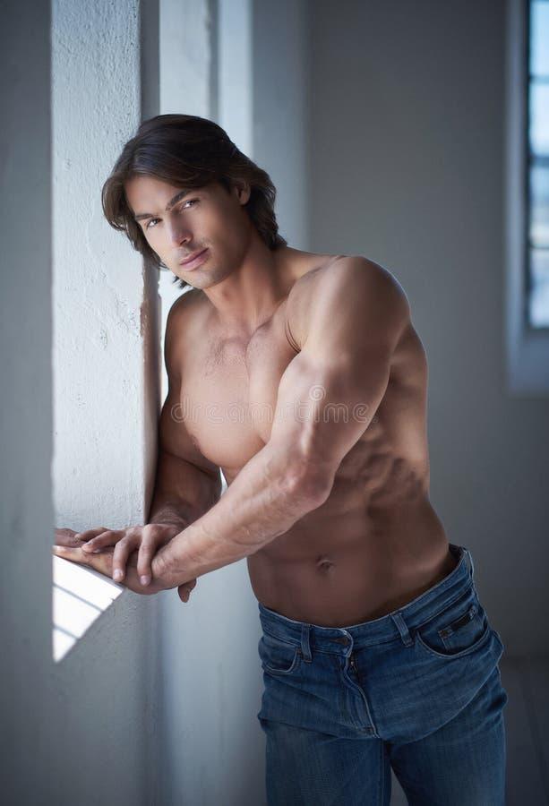 Shirtless stilig man med en perfekt benägenhet för muskulös kropp på en vägg i en studio som ser en kamera arkivfoton