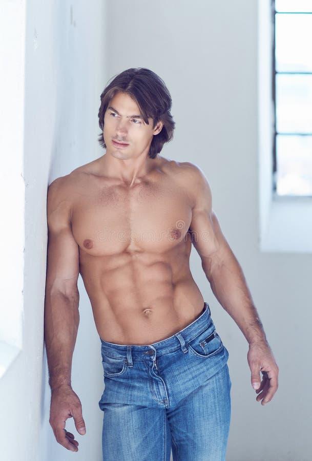Shirtless stilig man med en perfekt benägenhet för muskulös kropp på en vägg i studion som ser ett fönster arkivbilder