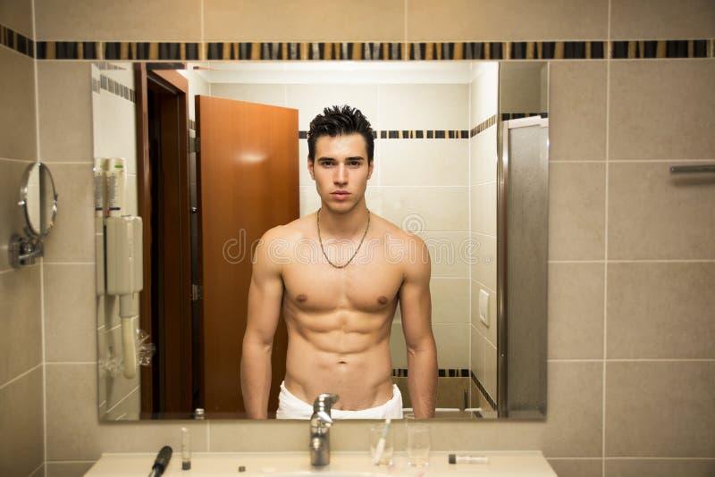 Shirtless stilig ung man i badrum royaltyfri bild