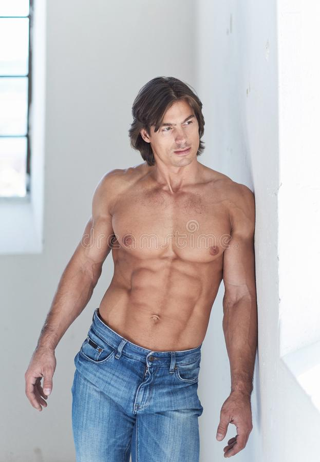 Portrait of suntanned muscular guy in denim jeans. Shirtless suntanned muscular male in denim jeans posing in natural day light stock photos