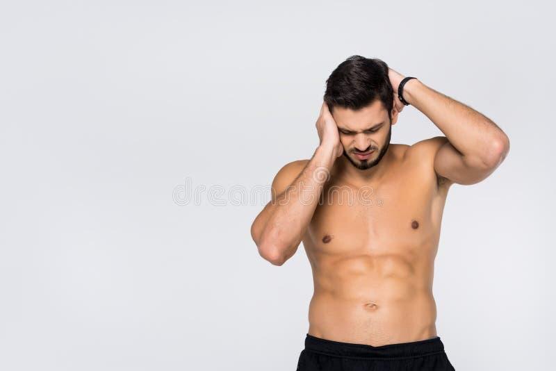shirtless ung idrotts- man med huvudvärk arkivfoto