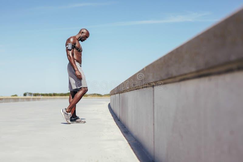 Shirtless ung idrottsman nen som kopplar av efter utomhus- genomkörare arkivfoton