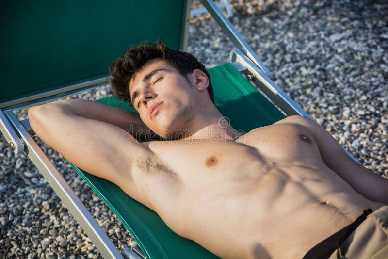 Shirtless ung man som solbadar i vardagsrumstol på royaltyfria bilder