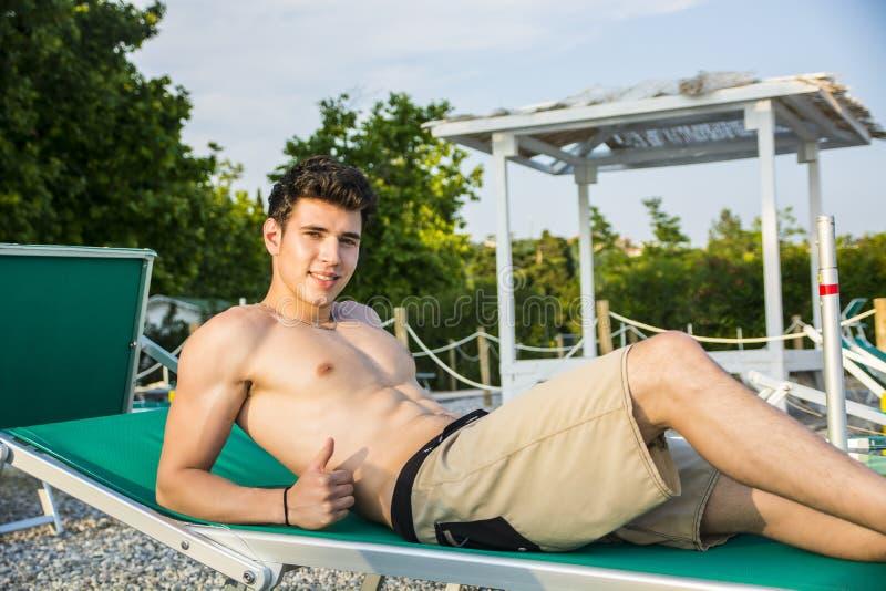Shirtless ung man som solbadar i vardagsrumstol på arkivfoto