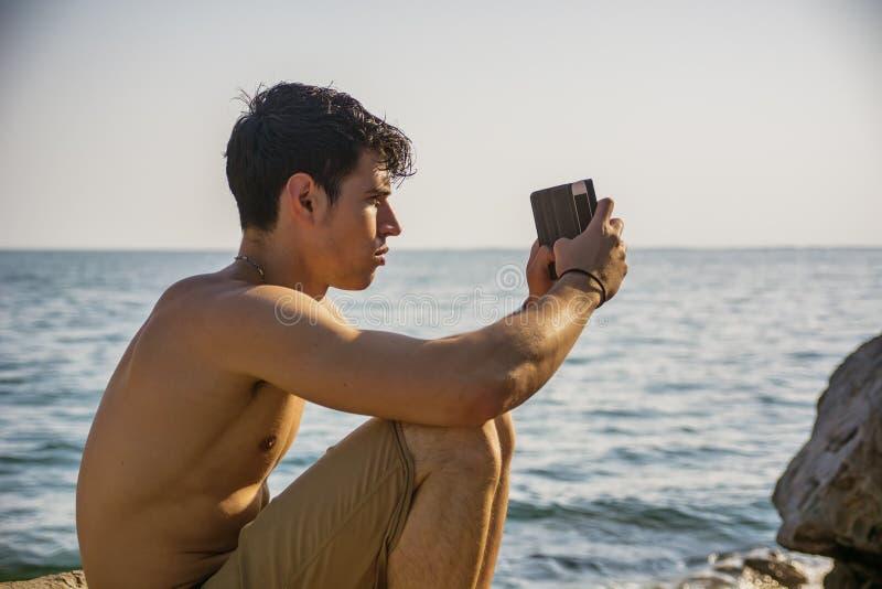 Shirtless ung man som tar foto på stranden royaltyfria foton