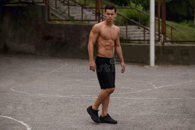 Shirtless ung sportive man som utanför poserar på sidan, på basketdomstolen som visar abs, en tonad kropp royaltyfri bild