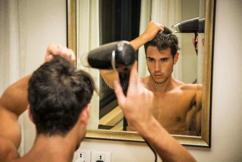 Shirtless uttorkninghår för ung man med hårtork fotografering för bildbyråer