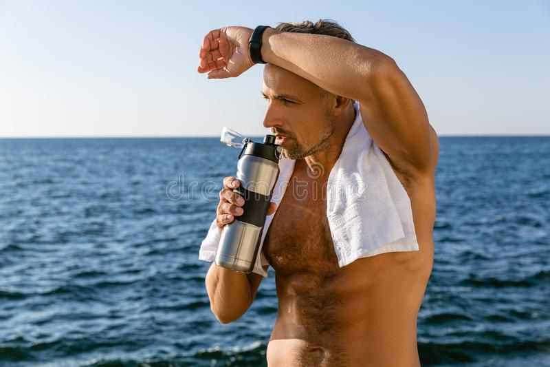 shirtless volwassen mens met handdoek op schouders drinkwater en afvegend zweet na training stock afbeelding