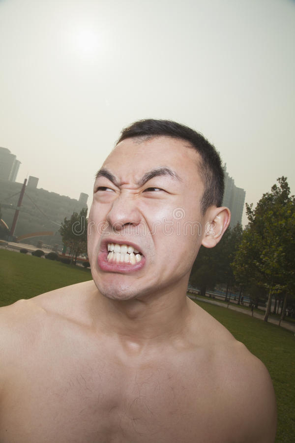 Shirtless young athletic man growling outdoors in a park in Beijing royalty free stock image