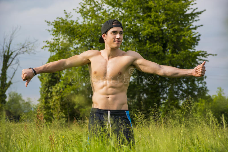 Topless young man with arms outstretched outdoors