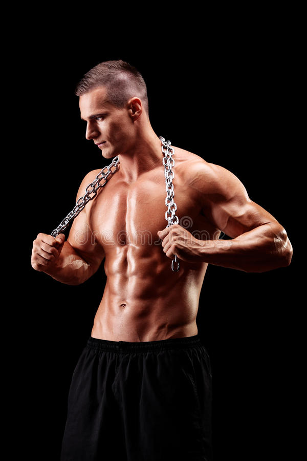 Shirtless young man holding a chain around his neck stock images