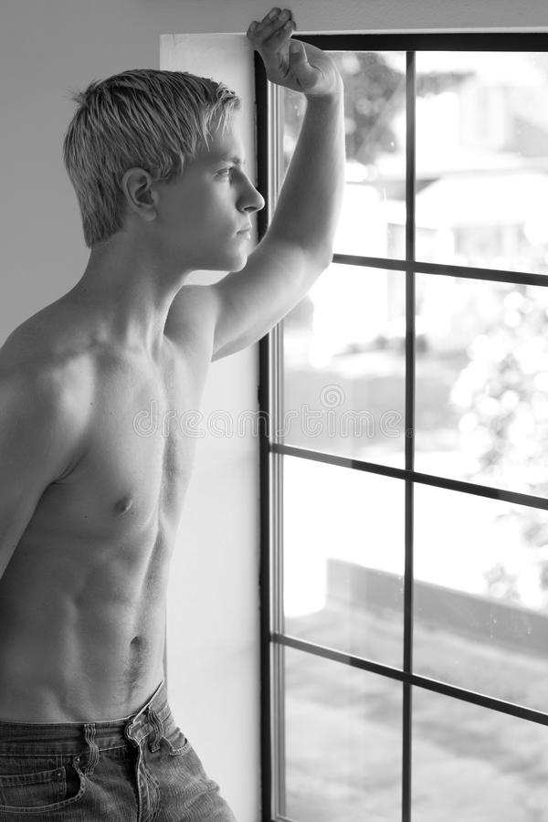 Shirtless young man looking out of the window royalty free stock photography