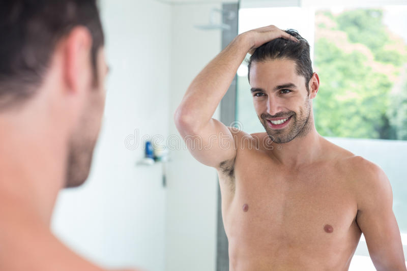 Shirtless young man smiling while looking in mirror royalty free stock photography