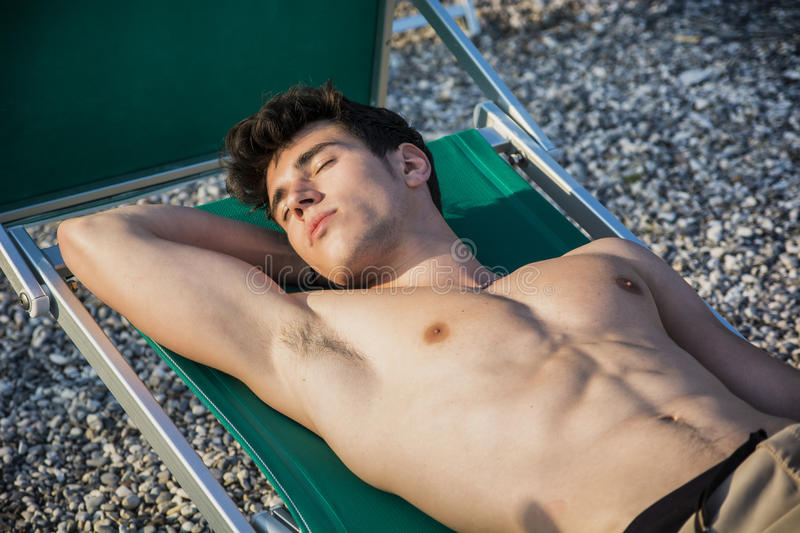 Shirtless Young Man Sunbathing in Lounge Chair on royalty free stock images