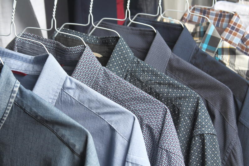 Shirts at the dry cleaners freshly ironed. Las camisas estan en perchas stock images