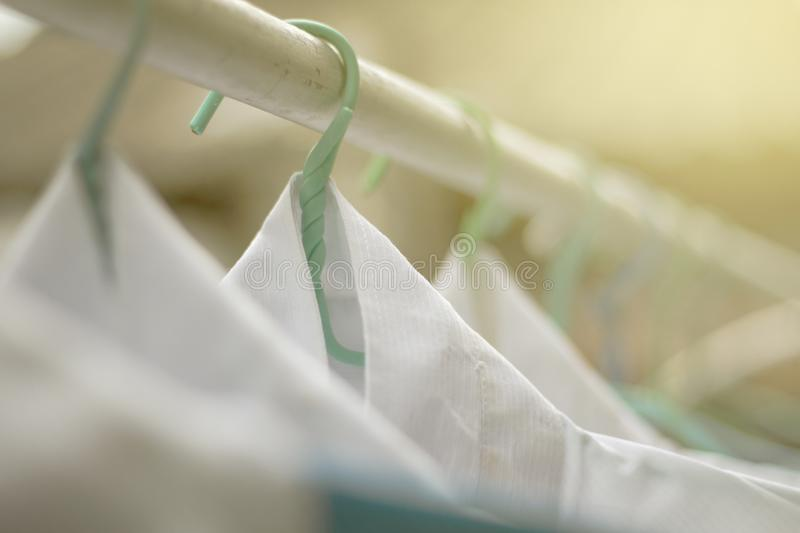 Shirts hanging on on open rail or clothes outdoors on laundry day. stock photo
