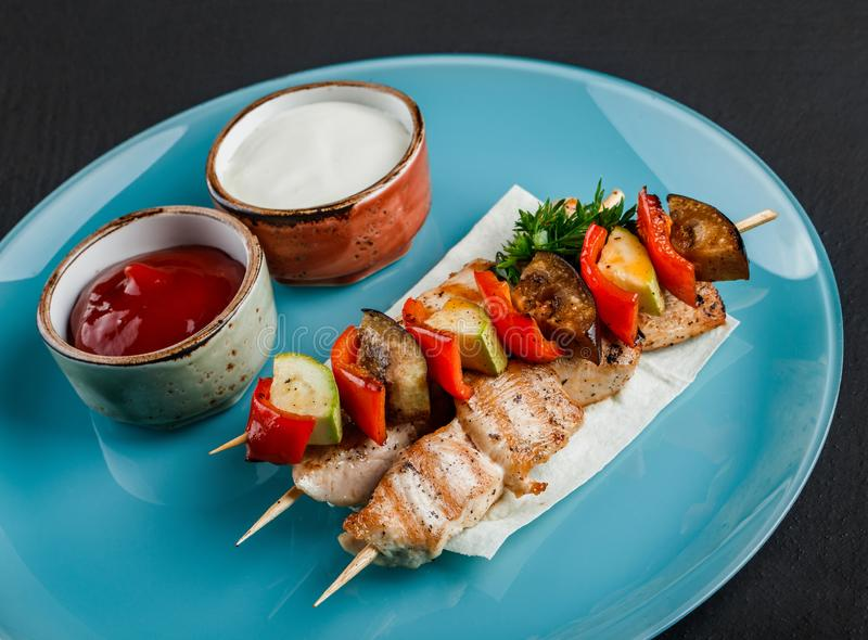 Shish grillat k?tt och gr?nsakkebab p? stekn?lar med s?s i platta ?ver m?rk bakgrund sund mat Varma k?ttr?tter, royaltyfri foto