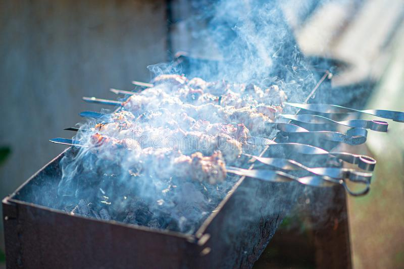 Shish kebab cooking in open air in summer. barbecue skewers fried on the grill in the smoke from the coals royalty free stock photos