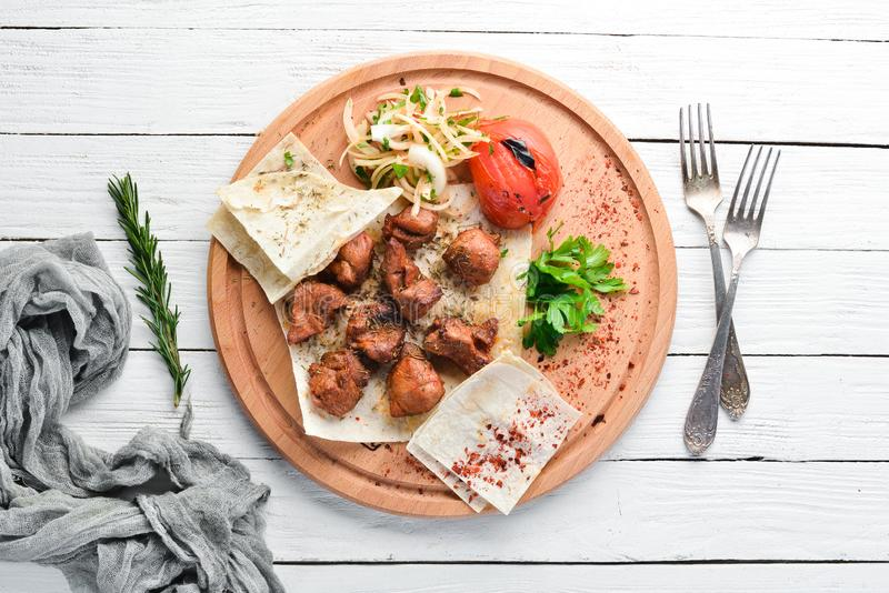 Shish kebab and grilled vegetables. On a white wooden background. stock photo