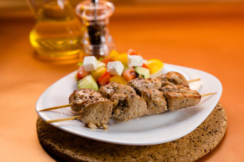 Shish kebab served on a plate with vegetable. Shish kebab served on white plate with fresh vegetables, black pepper and olive oil royalty free stock image