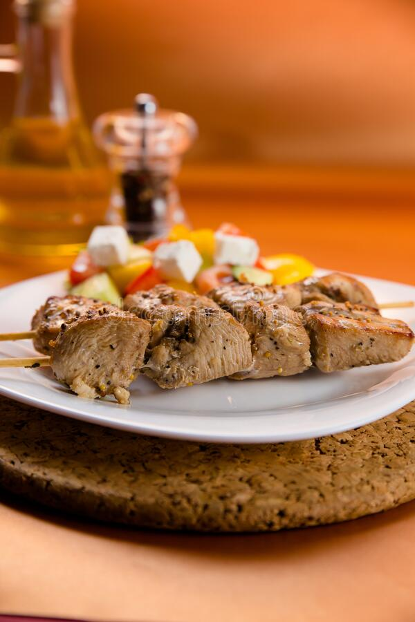 Shish kebab served on a plate with vegetable. Shish kebab served on white plate with fresh vegetables, black pepper and olive oil stock image