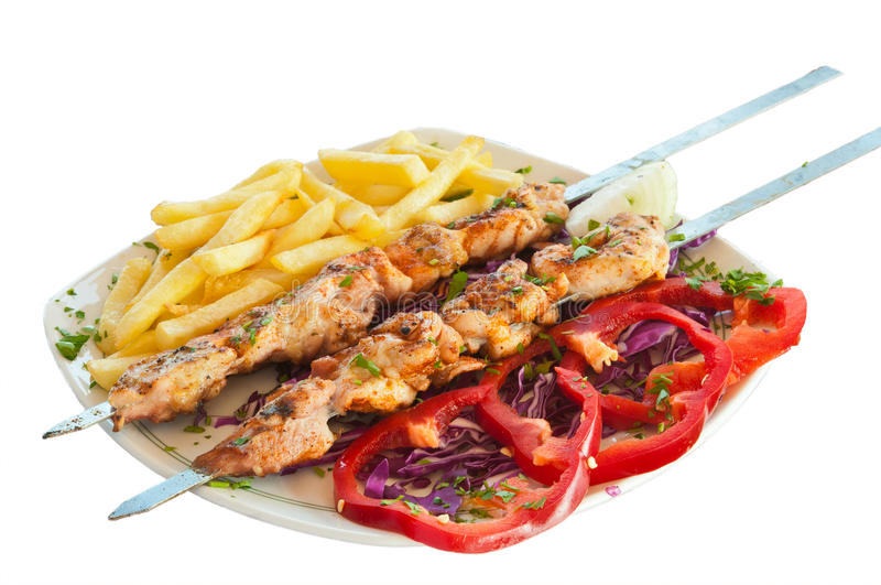 Shish kebab on skewers with chips. And red pepper pickled cabbage stock photography
