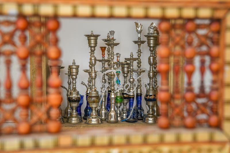 Shisha smoking pipes through oriental red wooden hand crafted wall window royalty free stock photo
