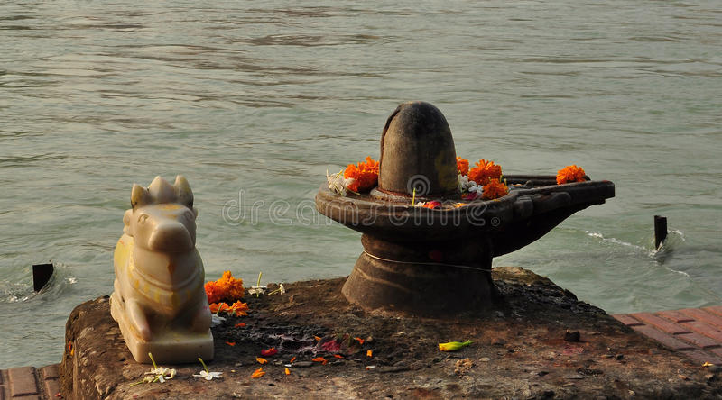 Shiva Linga and sacred bull statue on the Ganges river bank. Small Hindu shrine: Shiva Lingam and sacred bull with flowers on the Ganges river banks in Haridvar stock photos