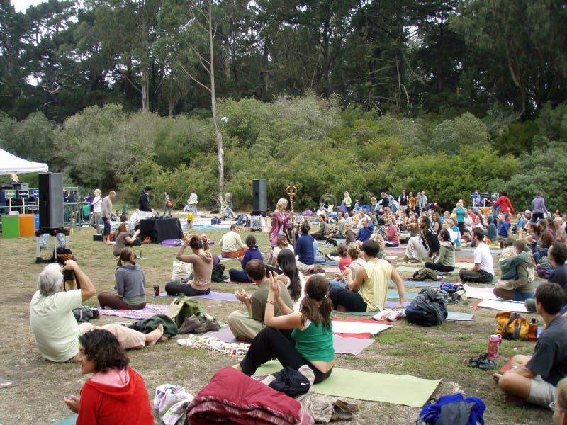 Shiva Rea uses stick to inspire yogis outdoors. SAN FRANCISCO, CA - SEPTEMBER 11: Shiva Rea uses stick to inspire yogis outdoors with michael franti at Power to royalty free stock photos