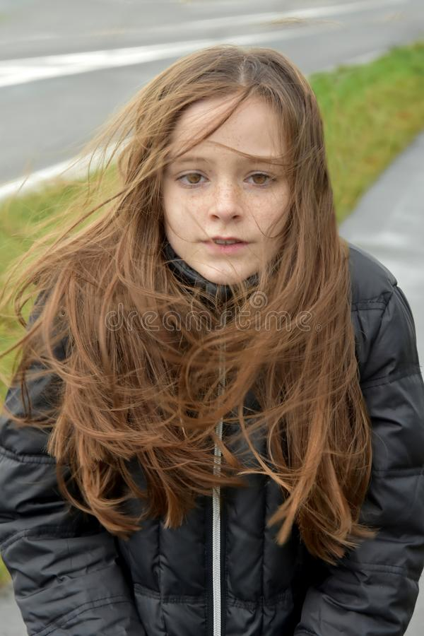 Shivering girl outside in stormy weather. Stormy weather, portrait of a shivering teenage girl outside with windswept hair stock images