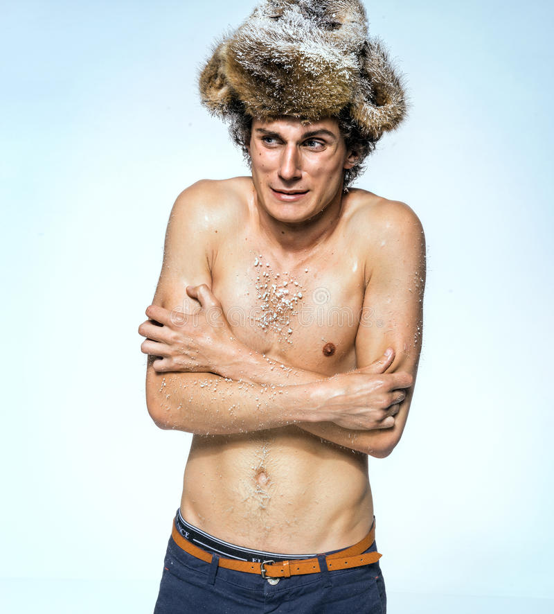 Shivering man frozen, because of bad winter heating. / trying to keep warm / image for winter heating related themes stock image