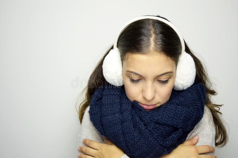 Shivering young woman looking down ill with flu or cold. Young woman being cold wearing earmuffs, scraf and sweater. Copy space. Shivering young woman looking stock image