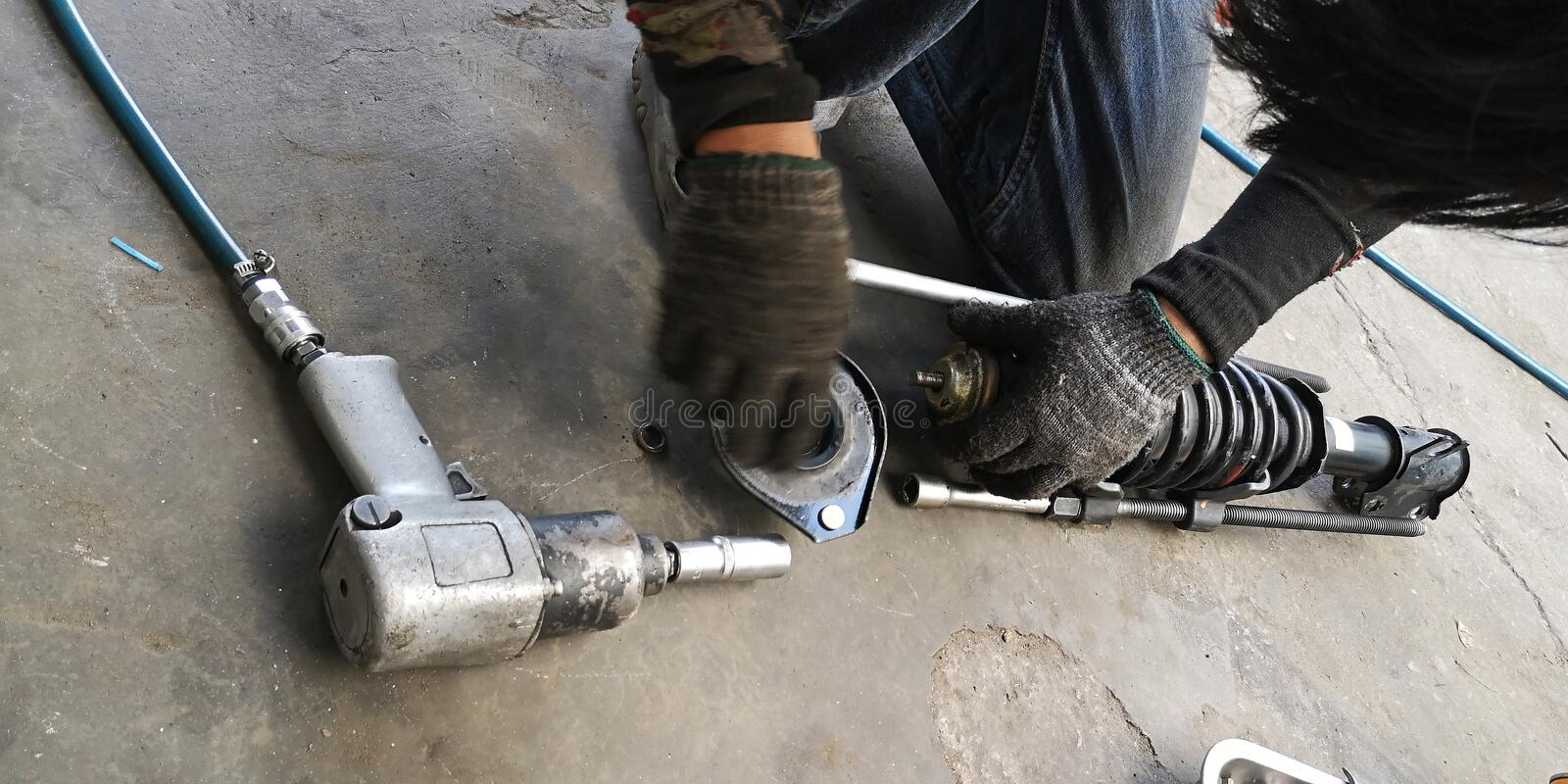 Shock absorber replacement is near has air gun tool by Asian mechanic royalty free stock photo