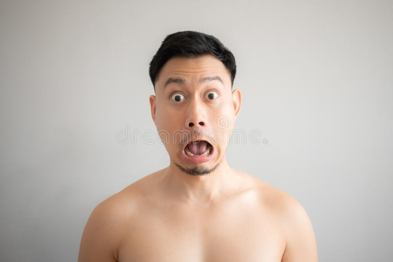 Shock and surprise face of Asian man in topless portrait isolated on gray background stock images